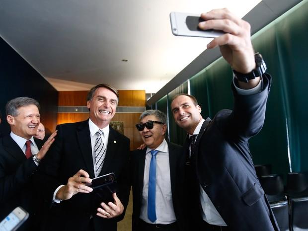 De férias e à paisana, o policial federal Newton Ishii posa para fotos com os deputados Eduardo Bolsonaro (PSC-SP) e Jair Bolsonaro (PP-RJ) durante visita ao plenário da Câmara dos Deputados, em Brasília