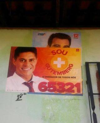 Cartaz de Gutemberg Braga por cima de um outro candidato