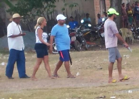 PM reformado ( de camisa azul) com arma na mão junto com capangas.