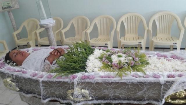 Mulher ficou o dia todo dentro do caixão com flores, objetos católicos e até maquiagem