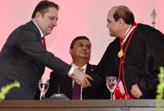 Presidente do TJ, Cleones Cunha, cumprimentando o procurador-geral Luiz Gonzaga no meio do governador Flávio Dino