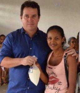 Fábio Torres, secretário de Desenvolvimento Social de Bacabeira, entrega leita à moradora