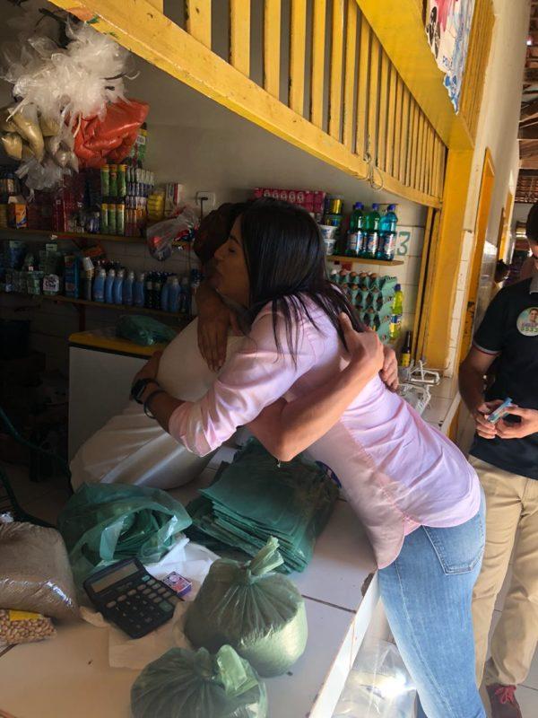 Daniella Tema recebendo o carinho de uma comerciante