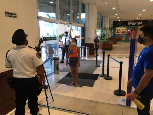 Funcionários de shopping no bairro Turu medem a temperatura de cliente em São Luís (MA)
