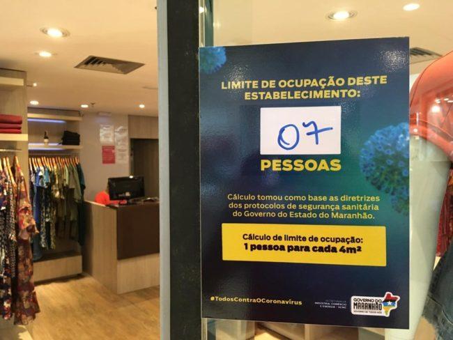 Cartazes indicam o limite de ocupação de pessoas permitido em uma loja no shopping de São Luís (MA)